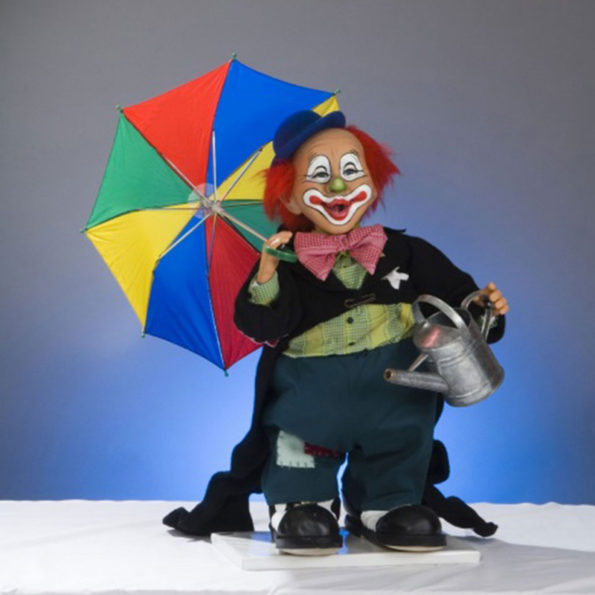 Clown with umbrella and watering can.
