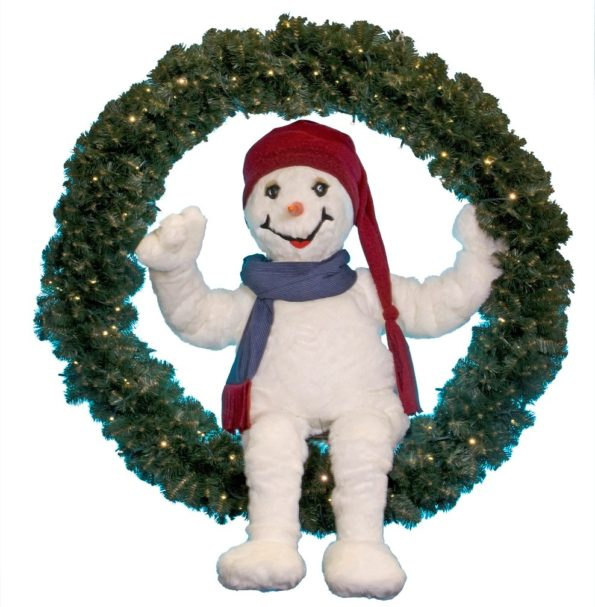 Snowman sitting in a fir wreath with lights.